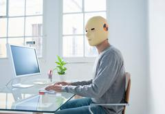 Man in crash test dummy mask in an office - stock photo