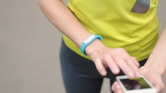 Women's hands with a sports bracelet and smart phone Stock Footage