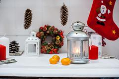 Christmas lantern, tangerines and socks on the dresser. - stock photo