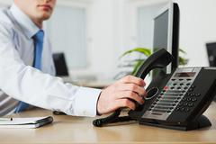 Office worker answering telephone Stock Photos