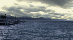 Waves splashing on choppy water surface, stormy cloudscape, mountains on horizon - stock footage