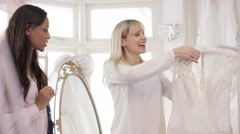 4K Bride to be shopping for wedding dress poses to have photo taken by friend Stock Footage