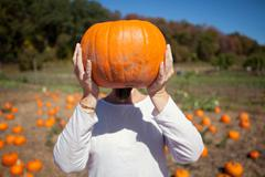 Person holding a pumpkin in front of face - stock photo