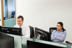 Bored businesswoman with male colleague in office Stock Photos