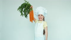 Girl chef holding carrots and smiling with teeth at camera. Thumb up. Ok Stock Footage