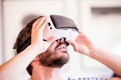 Man wearing virtual reality goggles, sitting in living room - stock photo