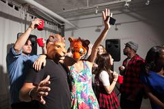 People wearing lion and tiger masks dancing at party - stock photo