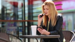 Beautiful blonde woman smokes electronic cigarette on the terrace of lovely cafe Stock Footage