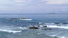 Sea with blue sky, clouds, waves and ship at the horizon in Galle, Sri Lanka. - stock footage