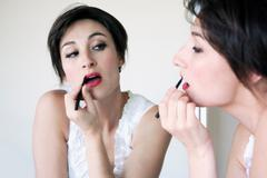 Woman applying lipstick in mirror - stock photo