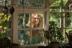 Woman looking through kitchen window - stock photo