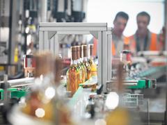 Wine bottles in bottling machine Stock Photos