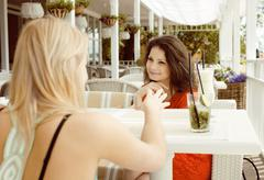 portrait of two pretty modern girl friends in cafe open air interior drinking - stock photo
