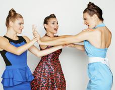 Three elegant fashion woman fighting on white background, bright dresses evil Stock Photos