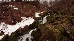 Water Flows Mountain Stream Washes the Moss-Covered Rocks Next to the Snow in Stock Footage