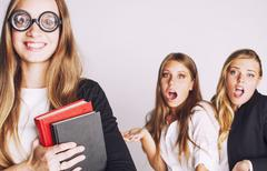 New student bookwarm in glasses against casual group on white, teen drama Stock Photos