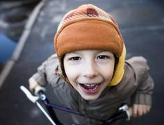 Little cute boy on bicycle smiling close up Stock Photos