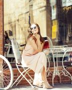 young pretty brunette woman after shopping sitting at cafe outside on street - stock photo
