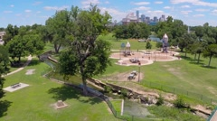 Fly up over play ground park and revealing City Skyline (Dallas) Stock Footage