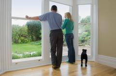 Couple and dog admiring new home - stock photo