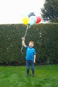 Smiling boy holding bunch of balloons Stock Photos