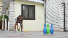 Five-year girl playing in a childrens bowling in the yard Stock Footage