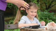 Girl looks in the picture is my mother braids in a ponytail her long hair Stock Footage