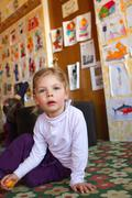 Girl sitting on floor in daycare - stock photo