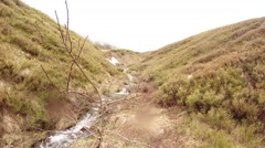 Small Mountain Stream Between Slopes of Hills in Highlands in Light Haze Stock Footage