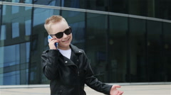 Baby boy 7 - 8 years in sunglasses with phone Stock Footage