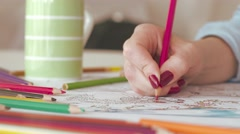 Woman coloring in adult coloring book at home - stock footage