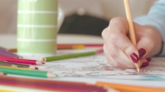 Woman coloring in adult coloring book at home Stock Footage