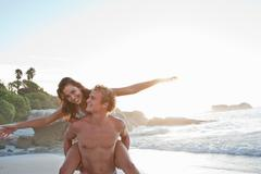 Man carrying woman piggyback on beach Stock Photos