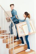 Couple moving boxes upstairs in new home Stock Photos