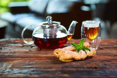 Tasty eclair and cup of tea on wooden table - stock photo