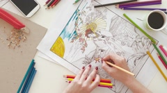 Top view of woman coloring in adult coloring book Stock Footage