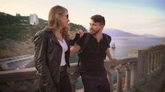The guy and the girl in a leather jacket, standing on the balcony overlooking Stock Footage