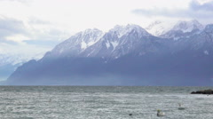 Amazing view of majestic snowy mountain range, cold stormy lake, windy weather - stock footage