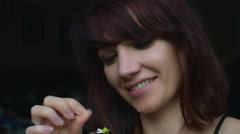 4k video of a woman outdoors taking petal off a flower - stock footage