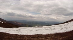 View From Snow-Covered Mountain Top on Valley Below Under Heavy Clouds Stock Footage