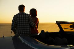 Couple admiring view on convertible - stock photo