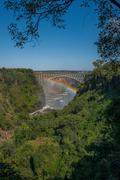 Rainbow spanning canyon beneath Victoria Falls Bridge - stock photo
