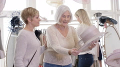 4K 3 female generations of a family shopping for outfits in a bridal wear store. Stock Footage