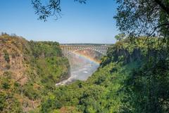 Rainbow spanning gorge beneath Victoria Falls Bridge - stock photo