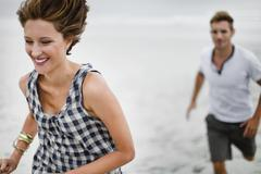 Couple chasing each other on beach - stock photo