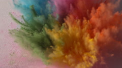 Colorful rainbow holi powder bounces off white canvas in shockwave, slow motion Stock Footage