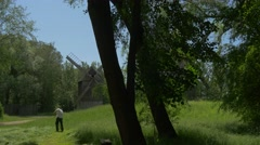 Peasant in a White Shirt Mows Fresh Green Grass on a Sunny Day in Near the Stock Footage