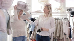 4K Young woman & grandmother pose for selfie while shopping in bridal wear store - stock footage
