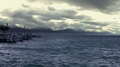 Slow motion of stormy waterscape, empty lakeside, heavy clouds above mountains Stock Footage