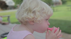 Cute Little Girl Trying To Blow Up Ballon Stock Footage